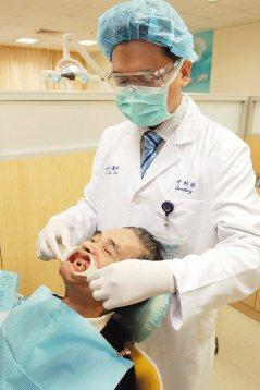 低收入戶林老先生上午在雙和醫院牙科主治醫師林錫奎(左)的幫助下,裝完全口活動假牙...