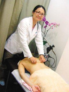 中醫師蔡蕙君示範「華佗夾脊術」,沿著脊椎兩旁俞穴往下提捏,手法輕柔有力道,捏到背...