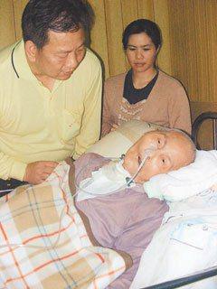 劉德樑(左)為了幫重癱老父親取得巴姓量表續雇外勞,每三年就得全家總動員,抬著老父...