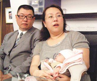 楊小姐抱著出生3個月大的女兒,與先生敘說高危險妊娠的危險經歷。 記者莊琇閔/攝影