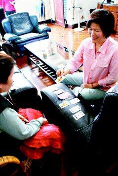 民間居家照顧服務內容多元,不僅是照顧,還包括陪伴,例如和老人家玩撲克牌。 圖/中...