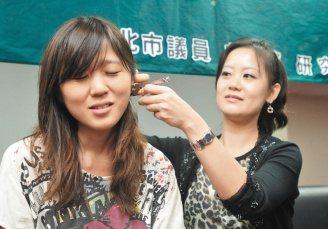 市議員吳思瑤(右)以網路購買的穿耳機假裝為助理穿耳洞,助理也緊張的皺起眉頭。 記...
