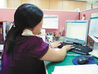 像這樣長時間的工作,盯著電腦或夾著電話,就有患頸椎椎間盤突出的危險。 記者彭芸芳...