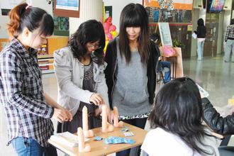 台灣首府大學昨天舉辦響應愛滋日的活動,教導學生正確使用保險套,女學生結伴參加,大...