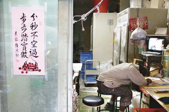 勞委會放寬「過勞死」的定義,希望有助減輕勞工負擔。圖為工人午休,與玻璃門上字句形...