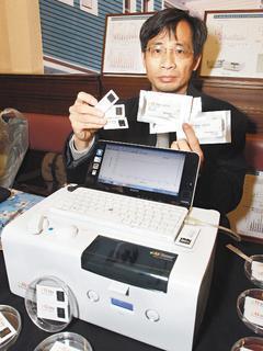 台大教授林世明展示可攜式癌症病毒定點診斷用儀器 「V感測儀」。 記者侯永全/攝影