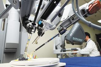 台北榮總昨天發表達文西機器手臂手術成果,醫師示範從主控台操作,利用視訊系統操控機...