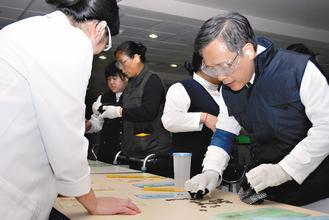 大林慈濟醫院院長簡守信(右)戴起磨砂眼鏡、手戴雙層手套等嘗試拿起零錢,體驗老人家...