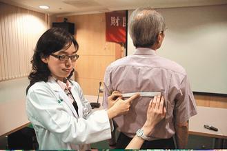 醫師葉怡嘉(左)昨教民眾自我檢測,以直尺放在兩肩胛骨的兩側,如尺斜了就是有長短腳...