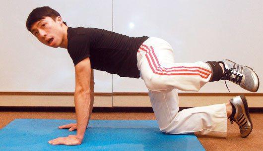 後踢腿:用膝蓋和前臂支撐身體,將右腿向上舉,儘可能抬高、向後伸展至最大角度。記者...