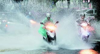 連日豪大雨,地上積水處處,汙水溢流,騎車或走在路上,小心水花濺傷眼。 本報資料照...