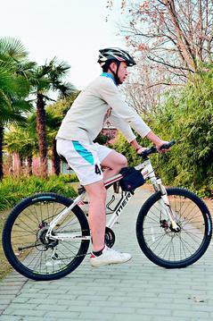 正確的騎車姿勢,腳跟踩在踏板上,膝蓋微彎接近伸直。 圖/林傑凱物理治療師提供