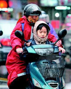 台北街頭到了下午明顯感受到低溫來襲,並且下起毛毛細雨,騎士紛紛穿上雨衣和厚衣禦寒...