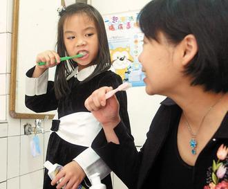 家長除了注意孩子口腔衛生,自己也要做好牙齒保健,才能防範蛀牙。 報系資料照片