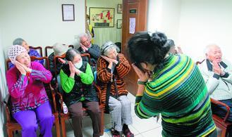 失智老人基金會的照護人員正帶領老人們邊唱邊玩。 記者侯永全/攝影