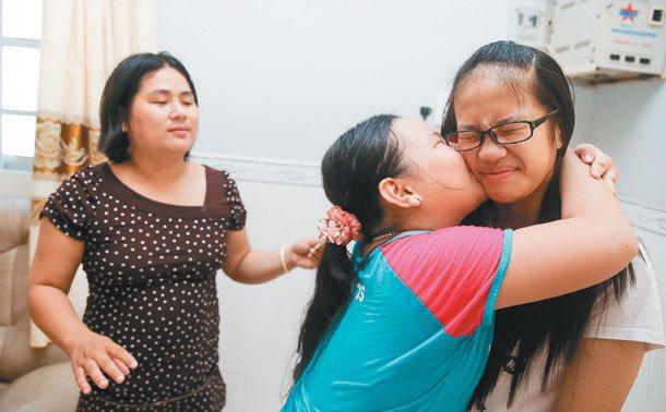 即將結束越南探親旅程返回台前夕,表妹潘睡維(左二)用力地親著周琬宜(右)的臉,滿...