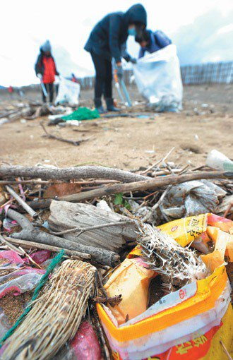 新北市金山區水尾漁港圓潭溪景觀橋旁的沙灘滿布塑膠袋等垃圾,其中還有兩隻小河豚的屍...