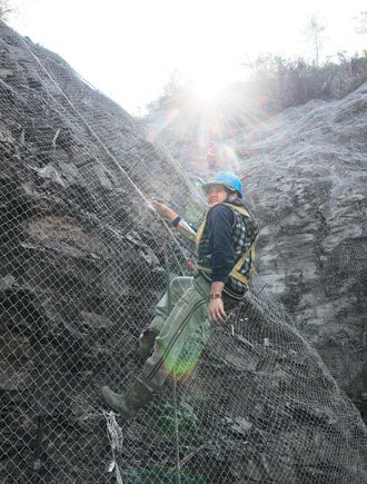 力行產業道路上方山坡,號稱蜘蛛人的工人在山壁上維護破碎的崩壁。 記者邱德祥/...
