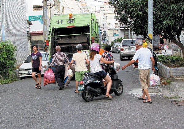 部分機車騎士不想等清潔車離開再通行,穿梭人群險造成擦撞。 記者鄭維真/攝影