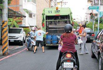 民眾騎車倒垃圾,稍不注意容易與行人擦撞。 記者鄭維真/攝影