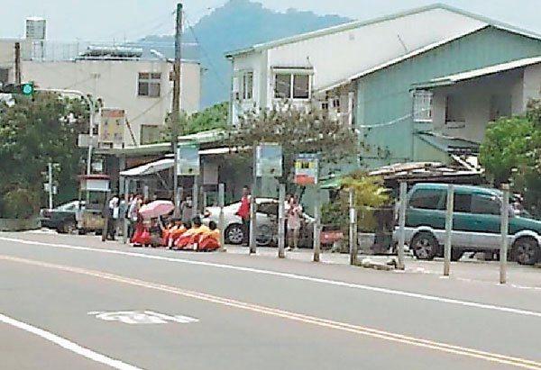 偏遠山區的學生苦坐在地上等待公車,有的還拿起陽傘遮日,怕天氣太熱會昏倒,路旁僅有...
