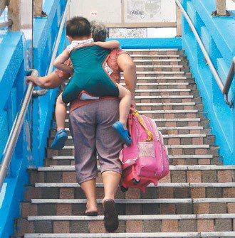 婦人背著小孩爬天橋過馬路,她每走幾步就休息一下,還得用手拉扶手。 記者游明煌/攝...