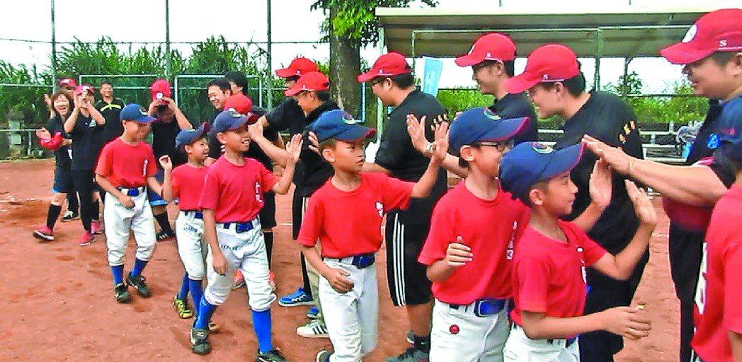 千秋國小棒球隊小球員開心地與家樂福文教基金會員工擊掌。 記者張家樂╱攝影