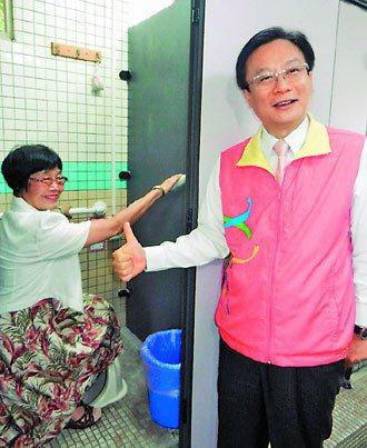 65歲退休教師王秀滿(左)體驗裝置安全扶手的校園友善公廁,十分滿意,縣長卓伯源很...