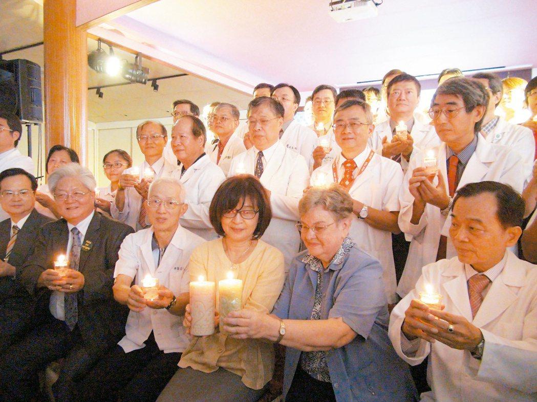 獲得雲林第一屆醫療奉獻獎的醫事人員,與縣長蘇治芬(前排右3)一起點亮手中燭光,盼...