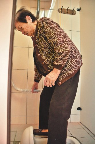 長者試用縣立體育場女廁後,認為加裝安全扶手,站起來方便多了。 記者林宛諭╱攝影