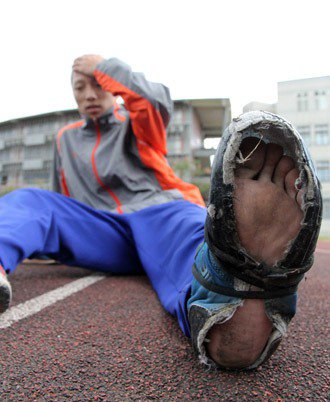 羅東高工球隊隊員的球鞋在PU跑道磨得破損不堪,有人練到鞋底掀開還在穿。 記者...