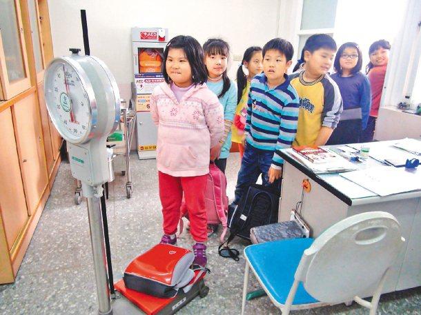 頭份鎮蟠桃國小每天上午,總有學生帶著書包到保健室「過磅」,檢查是否過重。 記者蘇...
