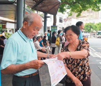 周文義和周黃桃,在台南火車站研究時刻表,討論要搭那一班車。 記者吳淑玲/攝影