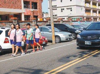 照南國中公教路側門旁停滿車輛,學生只能走在路旁。 記者張裕珍/攝影