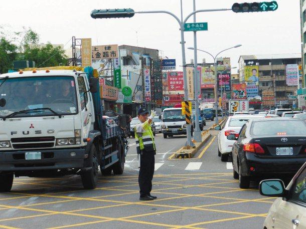 彰化市中央路分隔島缺口附近交通量大,車滿為患,員警指揮交通,維持動線順暢。 記者...