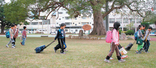 興隆國小學童背著、拖著書包上學。 記者胡蓬生/攝影