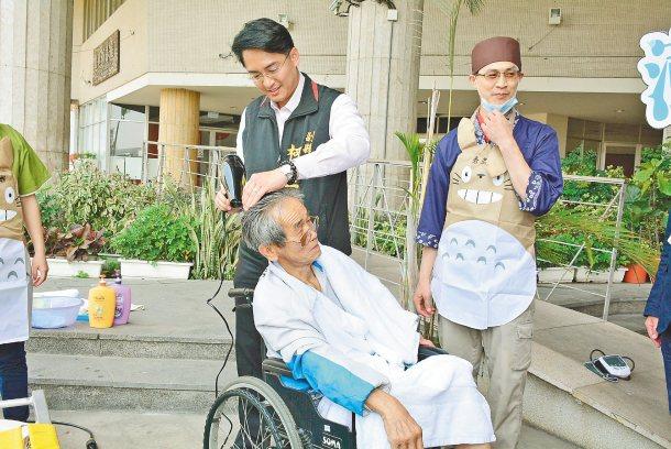 副縣長柯呈枋幫行動不便的老人家吹頭髮,希望營造對老人更友善的環境。 圖╱彰化縣政...