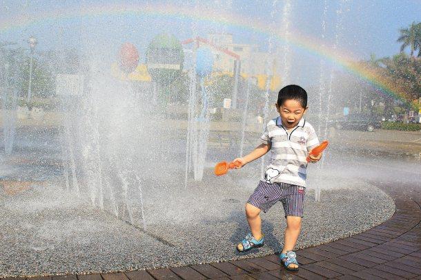 氣候悶熱,小孩子在家長陪同下,到市議會前的噴水池戲水,玩得不亦樂乎。 記者鄭宏斌...