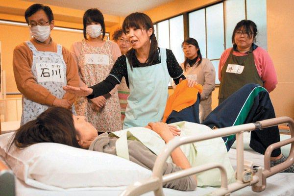 湘南學院介護職員初級研修班講師阿部繪美里,指導為臥床者放置尿壺的技巧。 東京記者...