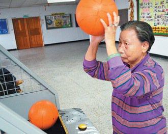 楊秋鳳在市立仁愛之家住了20年,平時最愛玩投籃機,是仁愛之家的「投籃高手」。 記...