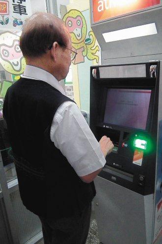 圖為行政院政務委員薛琦親自操作ATM提款機。 記者尤聰光╱攝影