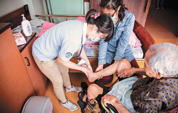 第一線服務人員替長輩擦拭乳液。 聯合勸募協會/提供