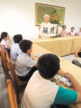 王敬之昨天拿出自己寫的「知足感恩」書法,提醒受助學童懂得惜福。 記者曹馥年╱攝影