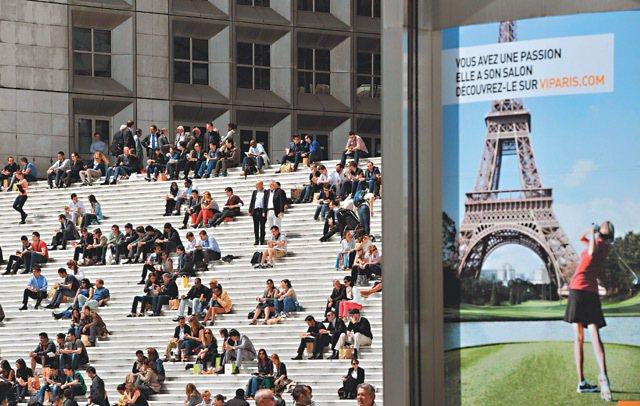 巴黎的金融區內,許多上班族中午坐在戶外享用午餐。 特派記者林澔一/巴黎攝影