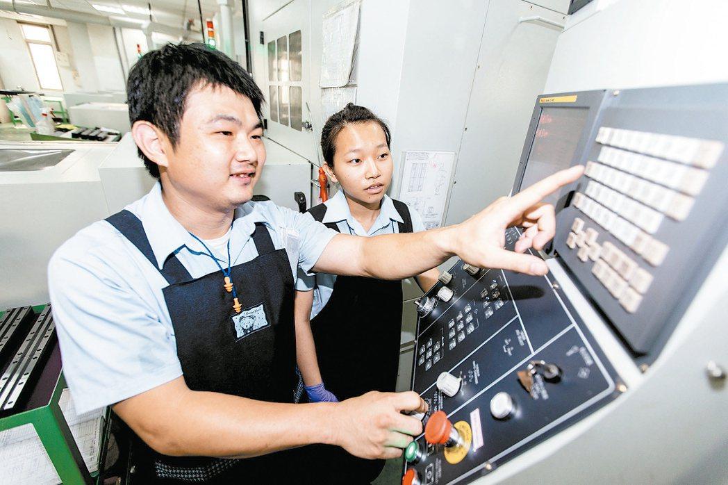 西螺農工高三學生葉芷岑(右),向師傅黃統港(左)學習機台加工原理與製程程式設定。...