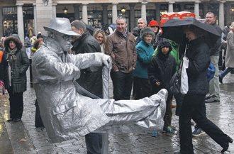 青年頂著零度低溫扮起街頭藝人,只為賺取一些零錢。 特派記者潘俊宏/攝影
