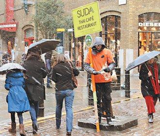 青年穿著薄衫,不畏飄雪在街頭當起人形立牌。 特派記者潘俊宏/攝影