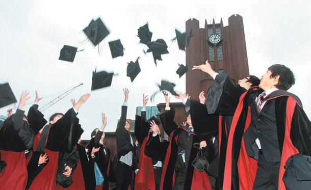 圖為一群東京大學畢業生,一起將學士帽拋向天空,慶祝順利畢業。 圖/聯合報提供