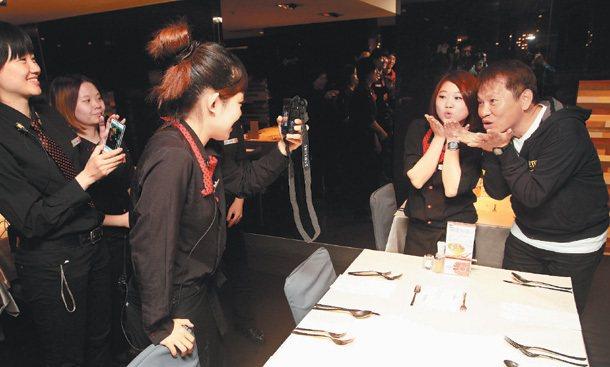戴勝益(右)到集團的分店,員工都搶著合照。 記者胡經周/攝影