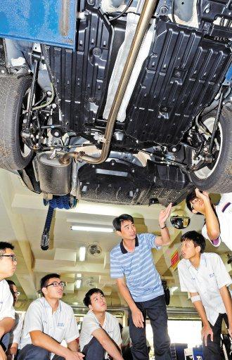 新北高工實習工廠汽修科老師楊國榮(中)指導學生保養油電混合車。 記者楊光昇/攝影
